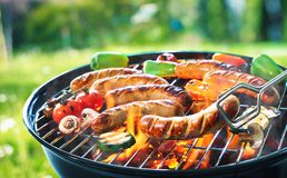Grilled sausage on the flaming grill. Grilled sausage on the picnic flaming grill Royalty Free Stock Image