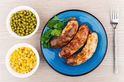 Grilled sausage in plate with parsley, green peas and corn Royalty Free Stock Photography