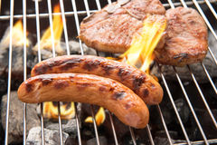 Grilled sausage and pork chop on the flaming grill Royalty Free Stock Images