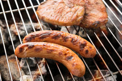 Grilled sausage and pork chop on the flaming grill Stock Image