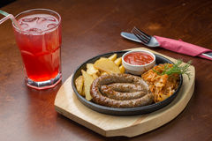 Grilled sausage. With potatoes and cabbage and glass of juice on wooden board on the table Royalty Free Stock Photo