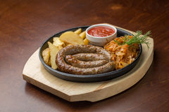 Grilled sausage. With potatoes and cabbage on wooden board on the table Stock Photos