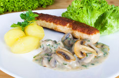 Grilled sausage with potatoes and mushrooms in cream Stock Photos