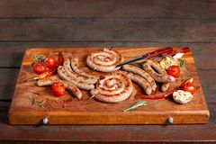 Grilled sausage ring on wooden board. Beautiful composition laid out on the board of natural wood. stock photos