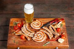 Grilled sausage ring on wooden board. Beautiful composition laid out on the board of natural wood. stock photography