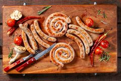 Grilled sausage ring on wooden board. Beautiful composition laid out on the board of natural wood. royalty free stock photo