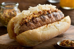 Grilled Sausage with Sauerkraut on a Bun. A delicious grilled sausage with sauerkraut and coarse mustard on a toasted hot dog bun Stock Photo