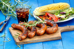 Grilled sausage and vegetables on a blue wooden background Royalty Free Stock Photo