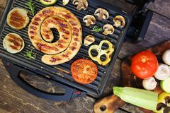 Grilled sausage and vegetables on the electric grill. Top view. Flat lay stock photo