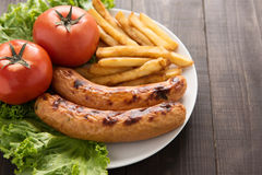 Grilled sausage and vegetables with french fries on wooden backg Stock Photo