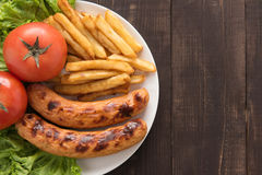 Grilled sausage and vegetables with french fries on wooden backg Royalty Free Stock Photography