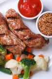 Grilled sausage with vegetables, ketchup and Dijon mustard.� Royalty Free Stock Photos