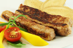 Grilled sausages. With vegetables and toasts Royalty Free Stock Photos