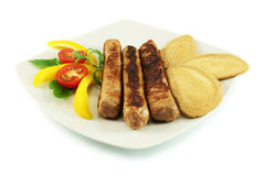 Grilled sausages. With vegetables and toasts Stock Images