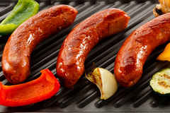 Grilled sausages. Group of grilled sausages and vegetables royalty free stock image