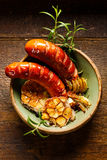 Grilled sausages with addition garlic, onion and rosemary on a rustic wooden table Royalty Free Stock Image