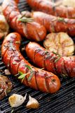 Grilled sausages with the addition of herbs and vegetables on the grill plate, outdoor, close-up. Grilled sausages with the addition of herbs and vegetables on stock photography