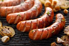 Grilled sausages with the addition of herbs and vegetables on the grill plate, outdoor, close-up. Grilled sausages with the addition of herbs and vegetables on royalty free stock images