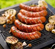 Grilled sausages with the addition of herbs and vegetables on the grill plate, outdoors. Grilling food, bbq, barbecue stock images