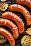 Grilled sausages with the addition of herbs and vegetables on the grill plate, top view, close-up. Grilling food, bbq, barbecue royalty free stock photos