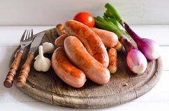 Grilled sausages. Assorted grilled sausages on rustic round wooden board royalty free stock photo