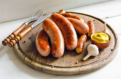 Grilled sausages. Assorted grilled sausages on rustic round wooden board royalty free stock image