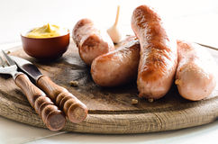 Grilled sausages. Assorted grilled sausages on rustic round wooden board stock photography