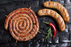 Grilled sausages assortment on a black background of charcoal. Barbecue grill. A stock images