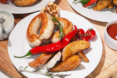 Grilled sausages with baked potatoes, cherry tomatoes and herbs Stock Photography