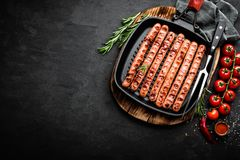 Grilled sausages bratwurst in grill frying-pan on black background. Top view. Traditional German cuisine. Stock image royalty free stock photography