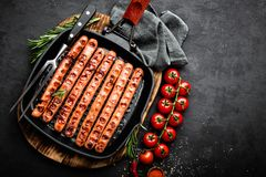 Grilled sausages bratwurst in grill frying-pan on black background. Top view. Traditional German cuisine. Stock image Royalty Free Stock Photo