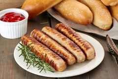 Grilled sausages with buns and sauce Royalty Free Stock Photos