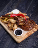 Grilled sausages and chicken with fries on a wooden. Board Stock Photo