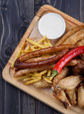 Grilled sausages and chicken with fries on a wooden stock image