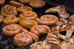 Grilled sausages and chicken wings Stock Photo