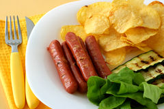 Grilled sausages with chips Stock Photography