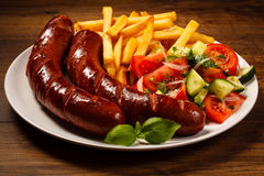 Grilled Sausages, Chips And Vegetable Salad Stock Photo
