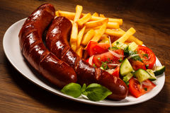 Grilled sausages, chips and vegetable salad Stock Photography
