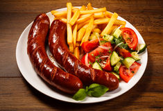 Grilled sausages, chips and vegetable salad Stock Images