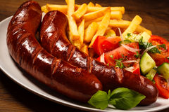 Grilled sausages, chips and vegetable salad Stock Photos