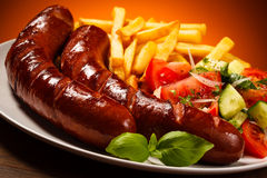 Grilled sausages, chips and vegetable salad Royalty Free Stock Image