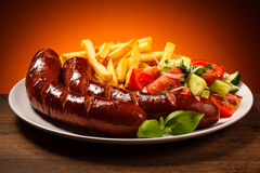 Grilled sausages, chips and vegetable salad Royalty Free Stock Photos