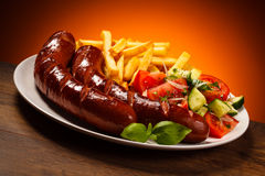 Grilled sausages, chips and vegetable salad Royalty Free Stock Images