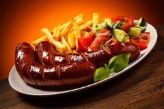 Grilled sausages, chips and vegetable salad Royalty Free Stock Photography