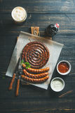 Grilled sausages and dark beer over scorched wooden background. Grilled sausages with sauces and glass of dark beer on rustic wooden serving board over dark Royalty Free Stock Images