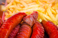 Grilled sausages with french fries on the background Stock Photos