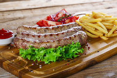 Grilled sausages with french fries Royalty Free Stock Photography