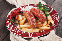 Grilled sausages with french fries Royalty Free Stock Image