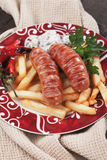 Grilled sausages with french fries Royalty Free Stock Photos
