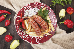 Grilled sausages and french fries Stock Photos